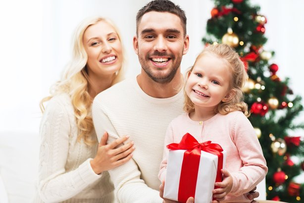 happy mother, father, and little daughter with gift box sitting on sofa at home