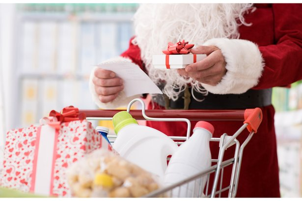 Santa Claus grocery shopping with a cart full of items, holding a list and a present