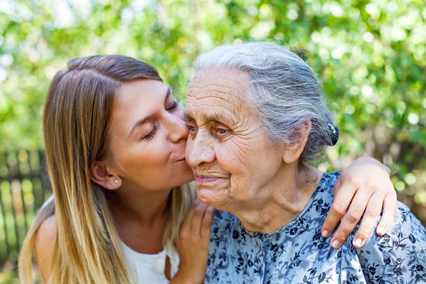young woman kissing grandmother on cheek