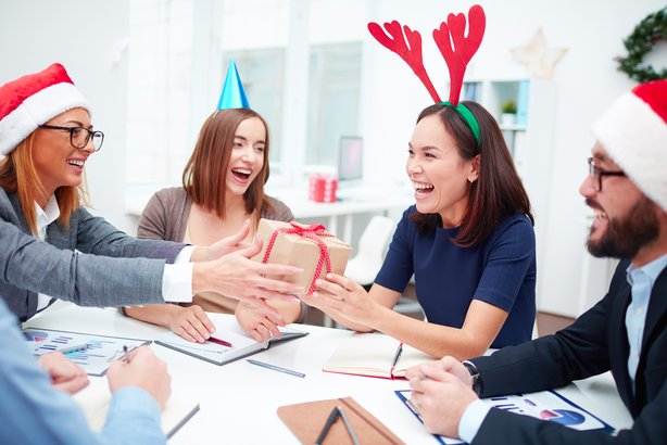 cheerful co workers exchanging christmas gifts in an office