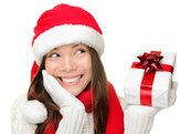 Happy young woman holding a present and looking sideways wearing a Santa hat
