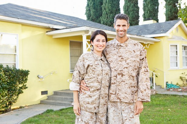 military couple in uniform standing outside house