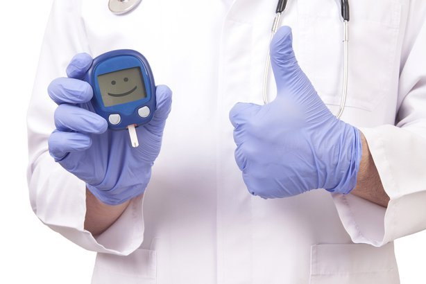 doctor holding blood sugar meter and showing 'OK' sign
