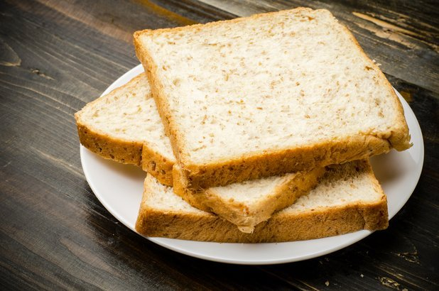 three slices of whole wheat bread on white plate and wooden table