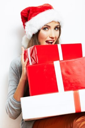 woman wearing santa hat with a pile of Christmas presents