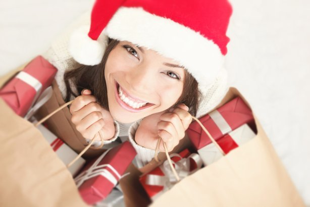 woman wearing santa hat looking up smiling with shopping bags full of Christmas presents