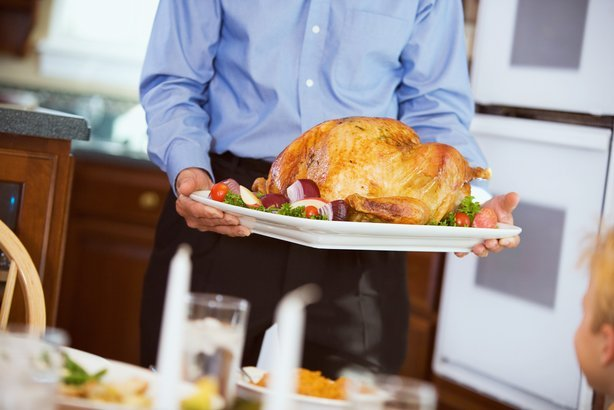 man brings roast Turkey brought to table on platter