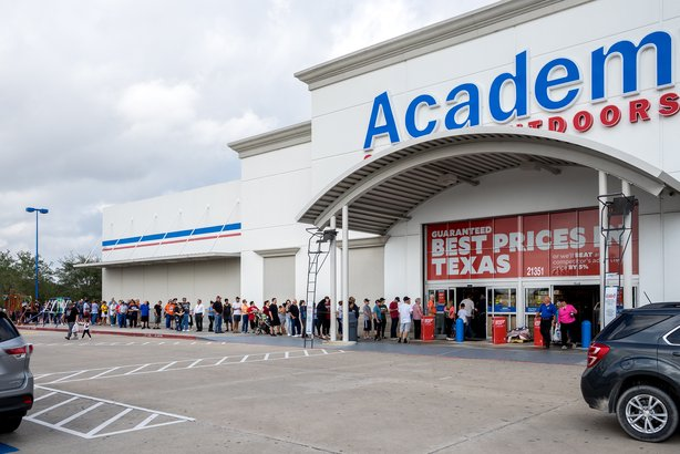 People waiting in a long line outside of an Academy store