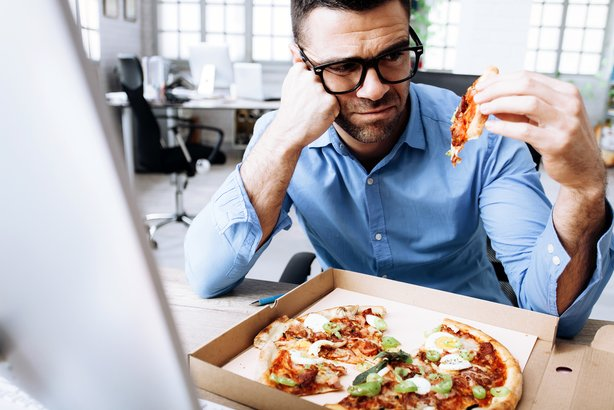 businessman having unpleasent pizza lunch break at workplace