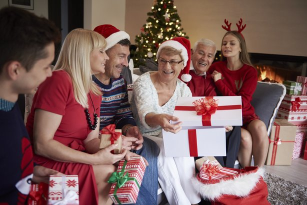 grandma opening present in front of christmas tree and family
