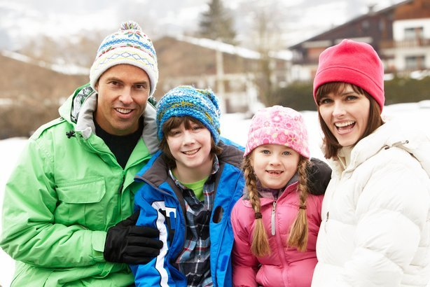 family wearing winter clothes in snowy landscape