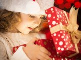 happy child in Santa hat opening Christmas gift box