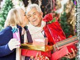 senior woman kissing man holding stacked Christmas presents at store