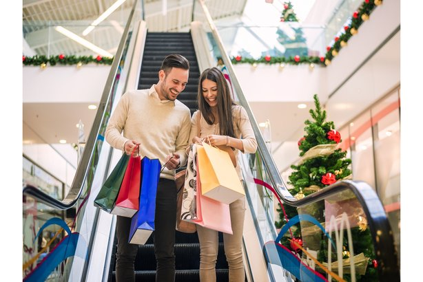 Happy young couple going down escalator in a mall during Christmas time with lots of shopping bags