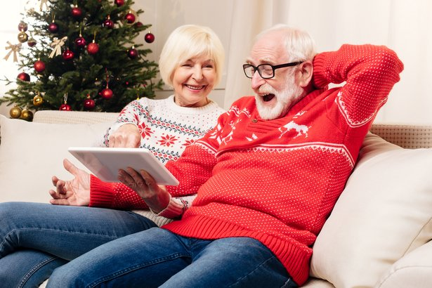senior couple sitting on the couch at home during christmas playing with a tablet