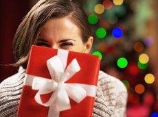 happy woman holding christmas present box in front of face