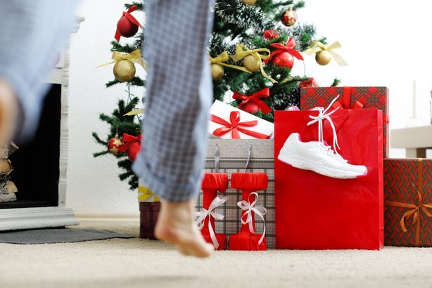 girl runs to the Christmas tree for athletic shoes and dumbbells gifts