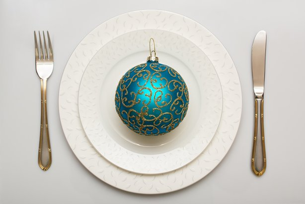Christmas ball on plate with fork and knife
