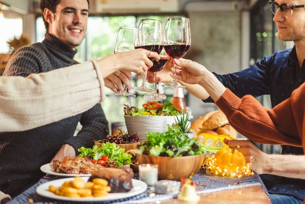 young people celebrating Christmas party dinner with clinking glass of wine