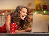 happy housewife with cup of hot chocolate using laptop in christmas decorated kitchen