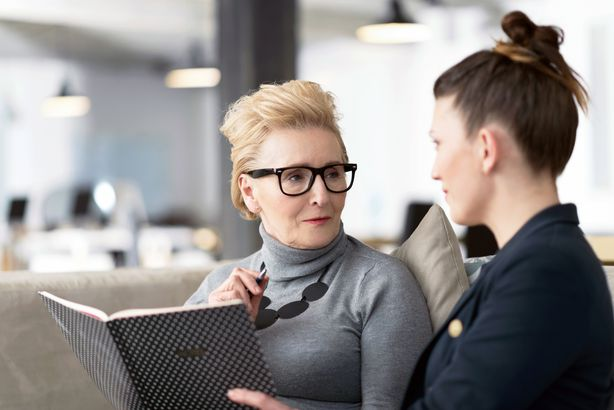 senior woman talking to coworker at office