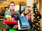 couple with Christmas presents and shopping bags in mall