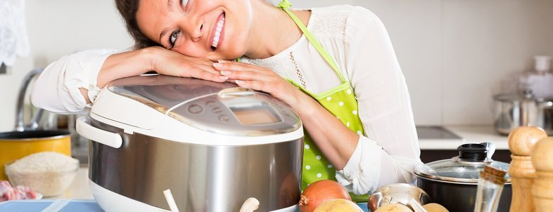smiling woman cooking with new slow-cooker in home
