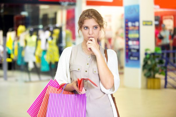 Young woman looking unsure holding open wallet in a mall while shopping