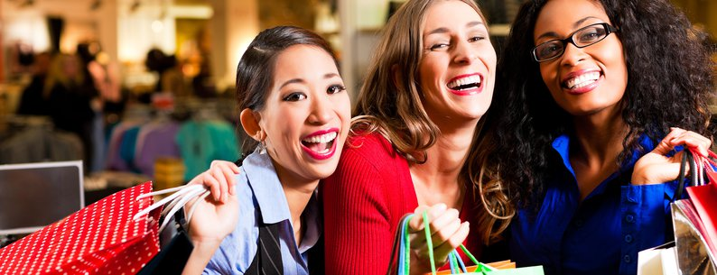 group of three women shopping in a mall