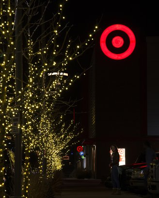 Christmas shopper pauses beneath red Target logo at night