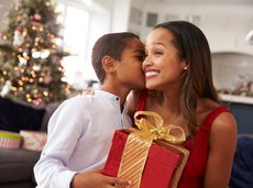 Happy mom receiving a gift and a kiss on her cheek from her young son on Christmas