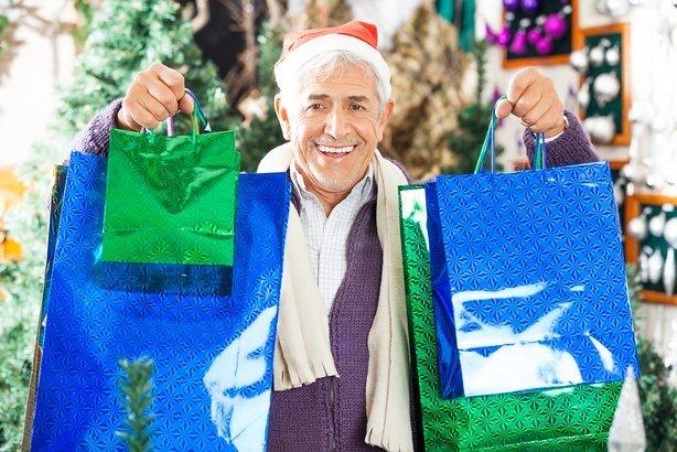 happy senior man carrying shopping bags at Christmas store