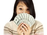 Woman holding U.S. dollars in front of face