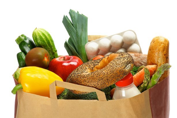 groceries bag with vegetables, bread, greens, fruits, bottle of milk and container of eggs