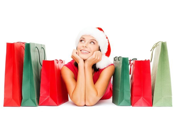 smiling woman in red shirt and santa hat with shopping bags
