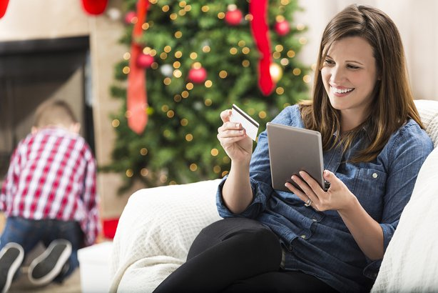 Woman sitting on couch with Christmas tree in background shopping on her tablet