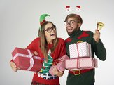 A young man and woman wearing tacky Christmas sweaters and acting silly