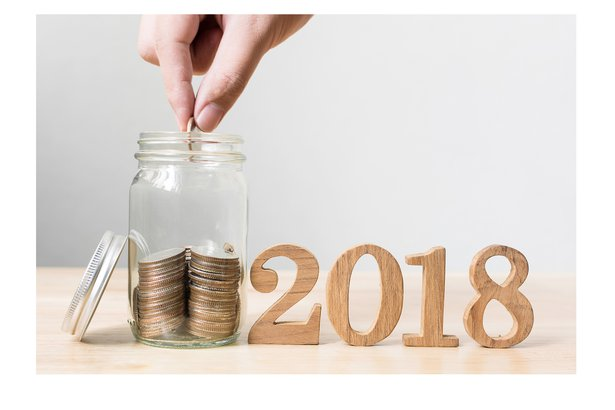 Hand putting coins into a jar next to wooden 2018 sign