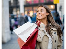 Woman smiling and shopping outside holding shopping bags