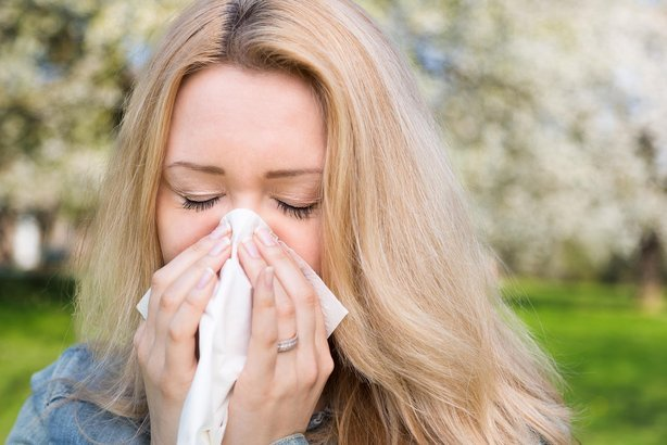 woman sneezing outside in spring