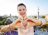 happy woman tourist showing heart shaped hand in Park Guell, Barcelona, Spain