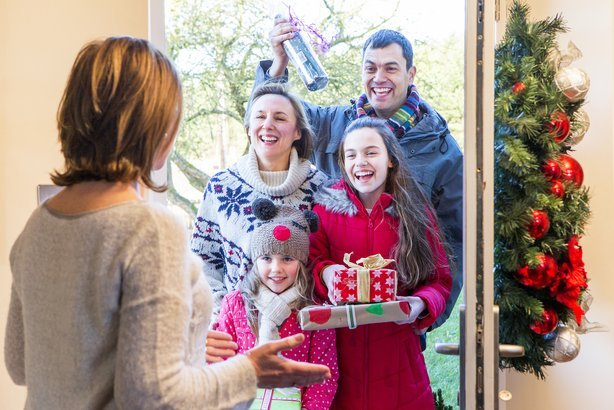 family delivering presents at Christmas time for the host