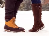 Closeup of man and woman's boots in the snow