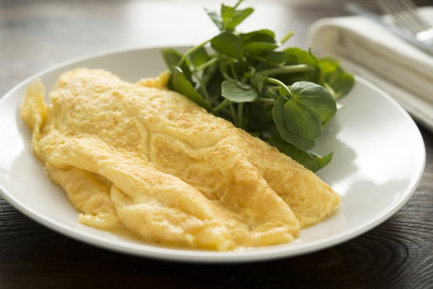 Plain omelet on a plate with greens