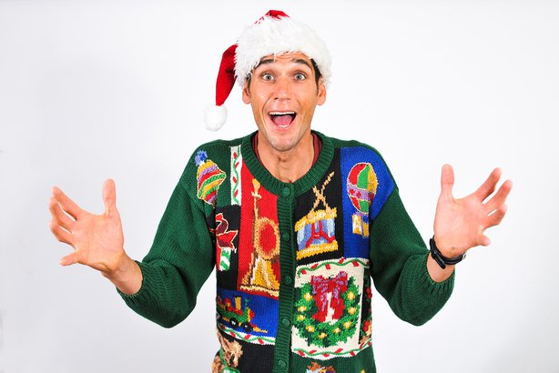 Goofy man smiling at camera with hands up wearing an ugly Christmas sweater
