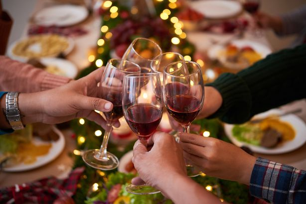 people at dinner table for the holidays, toasting glasses with red wine