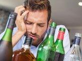 drunk businessman slumped beside many spirit bottles in apartment