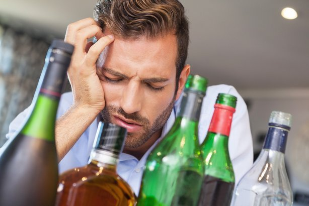 drunk businessman slumped beside many spirit bottles in apartment