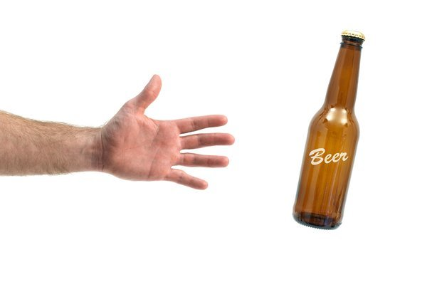 man's hand grabbing a beer bottle