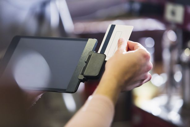 hand of woman sliding gift card through reader